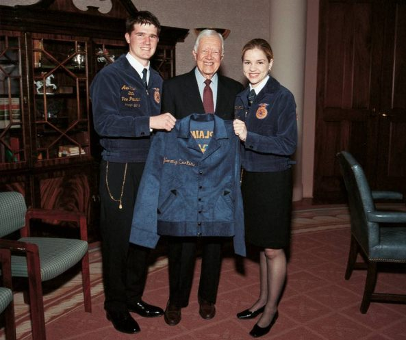 Former president Jimmy Carter stands with 2003 Georgia FFA Vice Presidents Rachael McCall and Alex Tolbert.